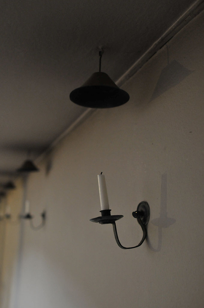 礼拝堂の中の壁をほのかに照らすための蝋燭たて